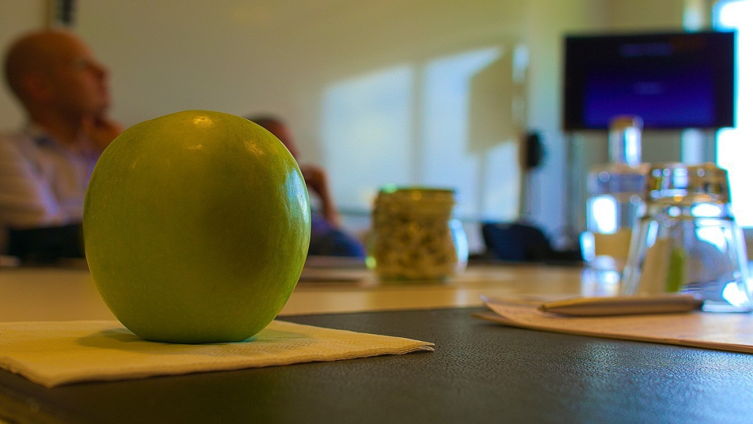 Picture of meeting table, with glasses and an apple.